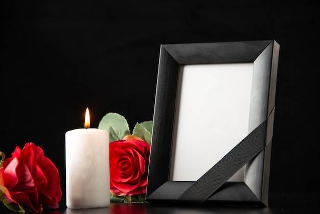 Vista frontal do porta-retratos com velas e flores vermelhas no escuro