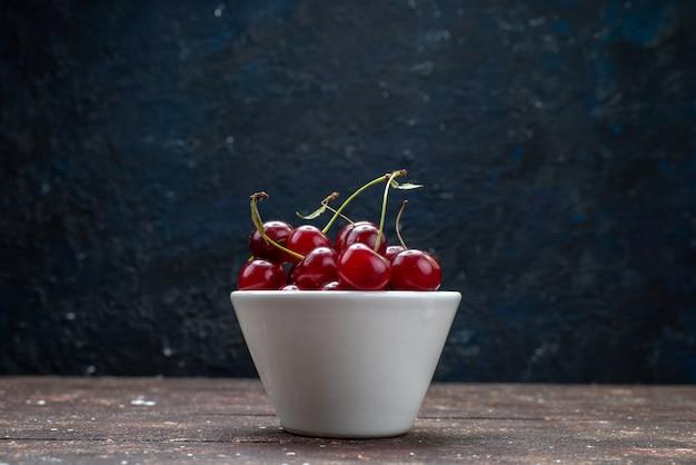 Vista frontal do prato branco com cerejas frescas vermelhas azedas na mesa de madeira marrom