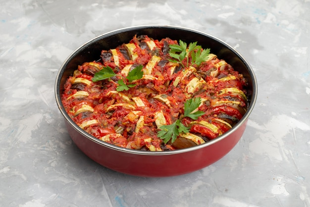 Vista frontal do prato de legumes cozidos dentro da panela na mesa brilhante