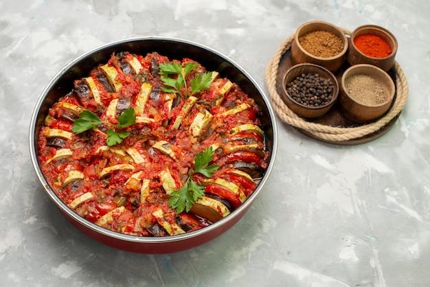 Vista frontal do prato de legumes cozidos dentro da panela redonda na mesa de luz