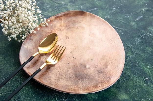 Vista frontal do prato marrom com colher dourada e garfo em fundo escuro