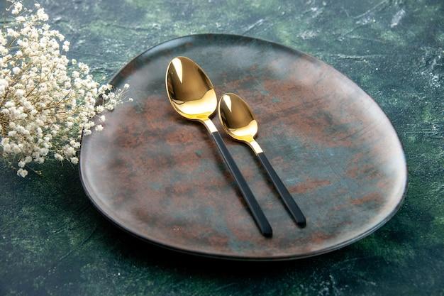 Vista frontal do prato marrom com colheres douradas em um fundo azul escuro