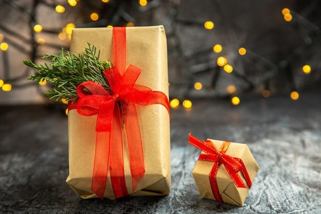 Vista frontal do presente de natal amarrado com fita vermelha em fundo escuro com luzes de natal