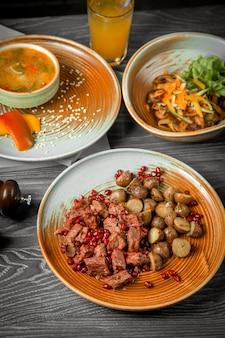 Vista frontal do primeiro segundo e prato principal sopa saladas de carne com batatas com um refrigerante em cima da mesa