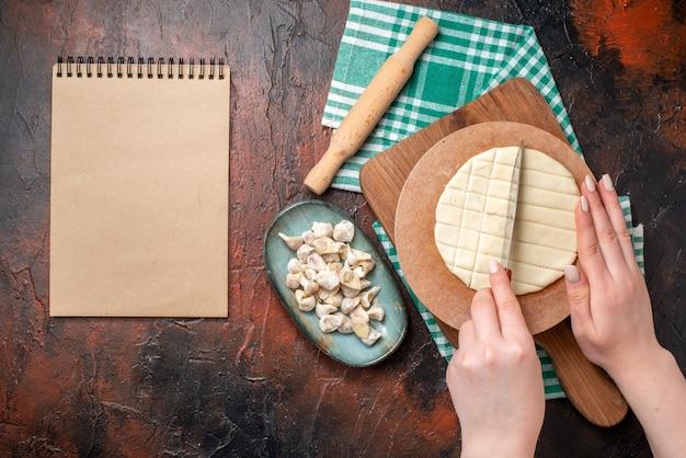 Vista frontal do processo de preparação de bolinhos de sopa dushbere, tábua de cortar rolo na toalha verde dobrada pela metade e caderno espiral na superfície escura
