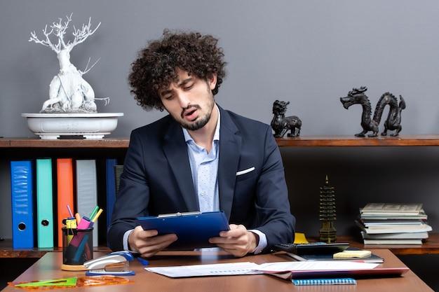 Vista frontal do processo de trabalho jovem trabalhador de escritório sentado à mesa