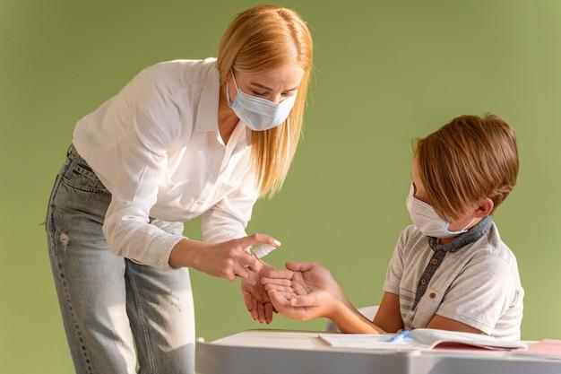 Vista frontal do professor com máscara médica desinfetando as mãos da criança na aula