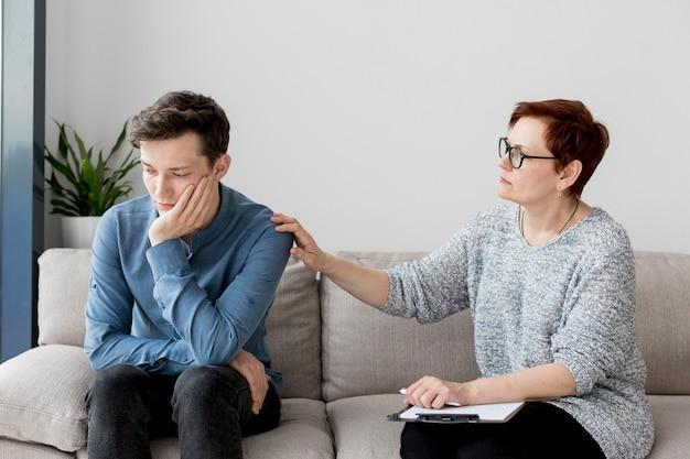 Vista frontal do psicólogo com paciente