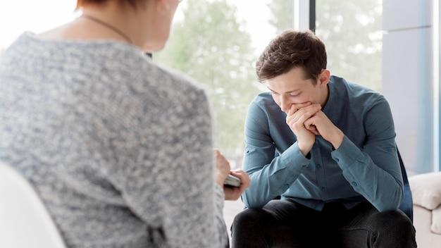 Vista frontal do psicólogo e paciente