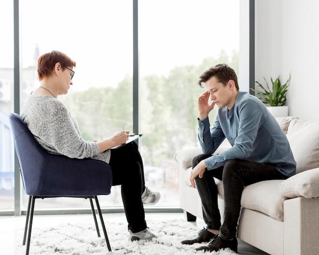 Vista frontal do psicólogo que consulta um paciente