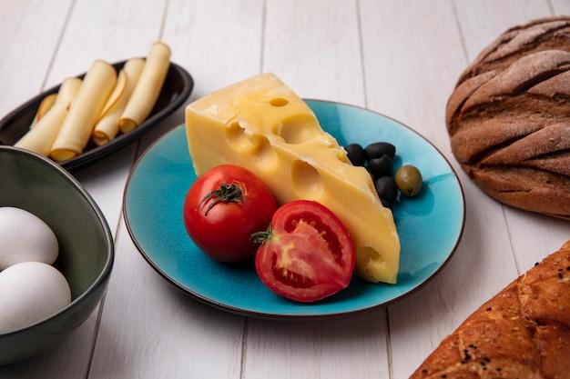 Vista frontal do queijo maasdam com tomates e azeitonas em um prato com ovos de galinha e um pedaço de pão preto e branco em um prato branco