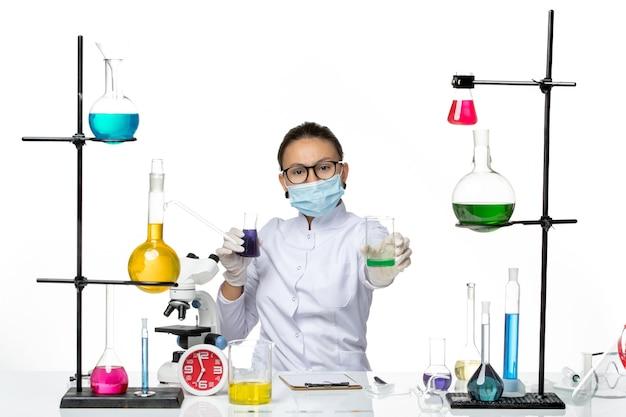 Vista frontal do químico feminino em traje médico com máscara segurando soluções diferentes no laboratório de química de vírus respingo de fundo branco claro-