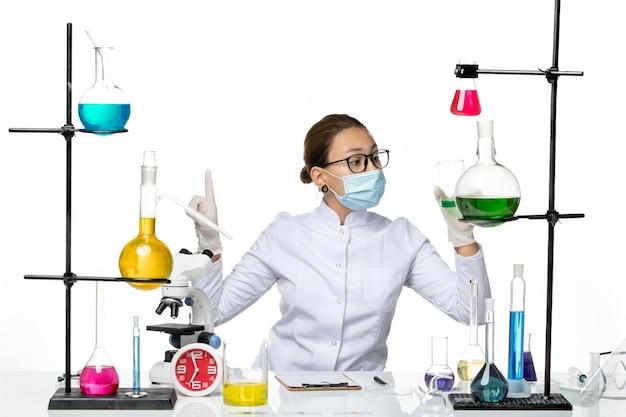 Vista frontal do químico feminino em traje médico com máscara segurando uma solução verde no laboratório de química de vírus respingo de fundo branco covid-