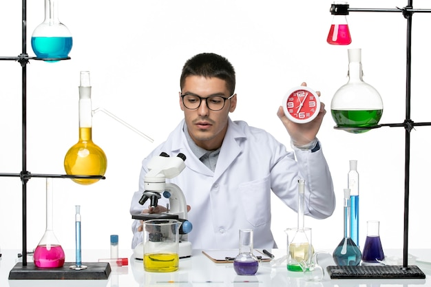 Vista frontal do químico masculino em terno médico branco segurando relógios no laboratório de ciência de vírus de covid-doença de fundo branco