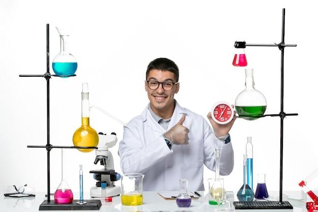 Vista frontal do químico masculino em terno médico branco segurando relógios sorrindo no laboratório de ciência de doenças de vírus cobiçoso de fundo branco