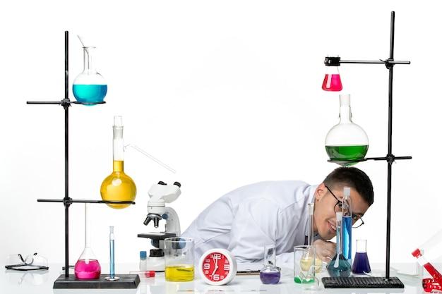 Vista frontal do químico masculino em terno médico branco sentado e se escondendo no laboratório de covidemia de ciência de vírus de fundo branco