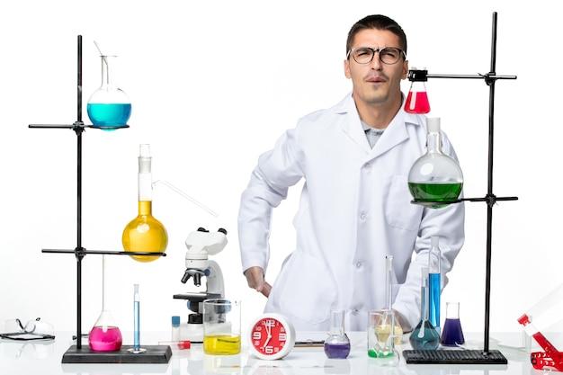 Vista frontal do químico masculino em traje médico branco dentro da sala com soluções em fundo branco laboratório vírus ciência covid pandemia
