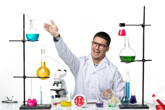 Vista frontal do químico masculino em traje médico branco sentado e se preparando para trabalhar no laboratório de covidemia de ciência de vírus de fundo branco