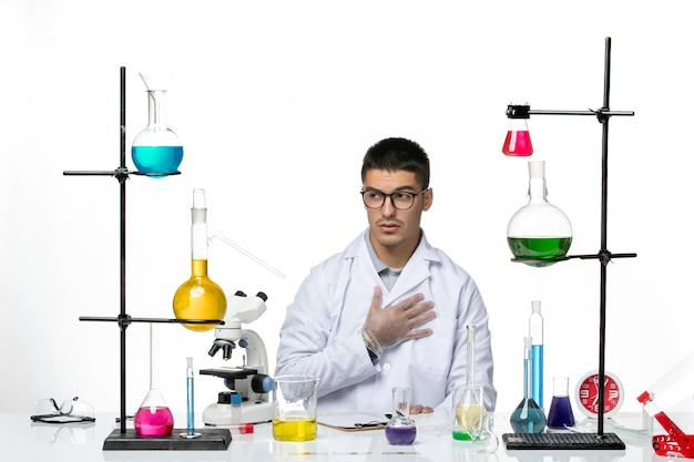 Vista frontal do químico masculino em traje médico sentado com soluções sobre a ciência da doença covid do vírus de fundo branco claro