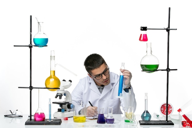 Vista frontal do químico masculino em traje médico sentado e segurando a solução escrevendo notas sobre fundo branco vírus covid- respingo de doenças ciência