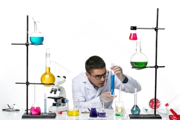 Vista frontal do químico masculino em traje médico sentado e segurando a solução sobre a ciência de doenças de vírus covid- splash de fundo branco
