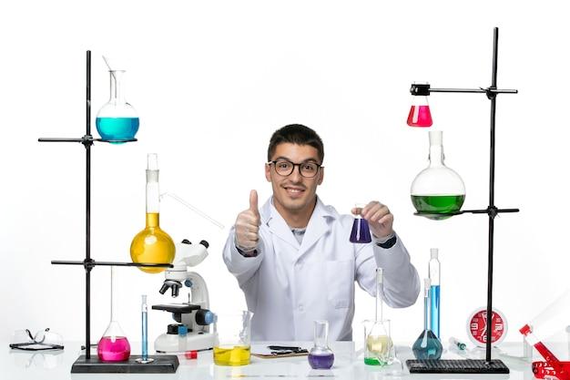 Vista frontal do químico masculino em traje médico sentado e segurando o frasco com solução no fundo branco vírus covid respingo doença ciência