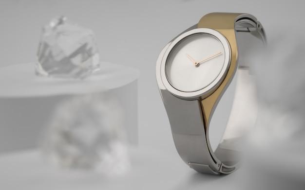 Vista frontal do relógio de mão em ouro design moderno prata entre brilhantes em branco