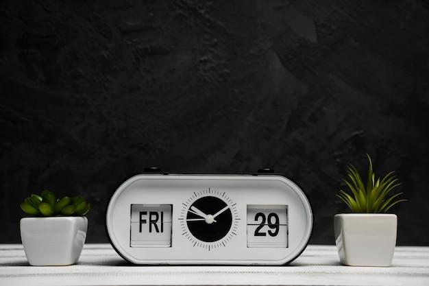 Vista frontal do relógio e lâmpadas com mesa de madeira