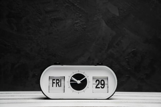 Vista frontal do relógio na mesa de madeira