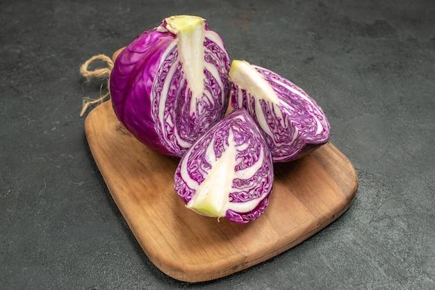 Vista frontal do repolho roxo fresco cortado na mesa escura salada madura, dieta saudável