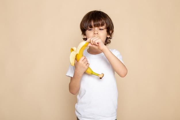 Vista frontal do retrato, garotinho fofo adorável em camiseta branca descascando bananon rosa