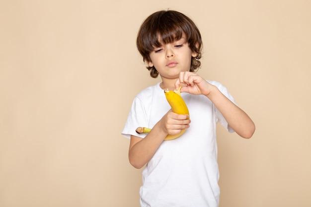 Vista frontal do retrato, menino bonitinho adorável em camiseta branca com parede rosa bananon