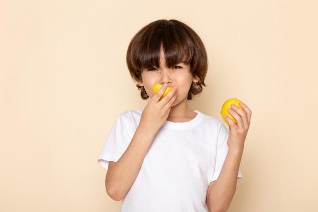 Vista frontal do retrato, menino comendo limão rosa