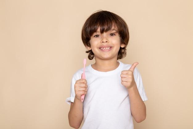Vista frontal do retrato, sorridente menino fofo adorável doce em camiseta branca na parede rosa