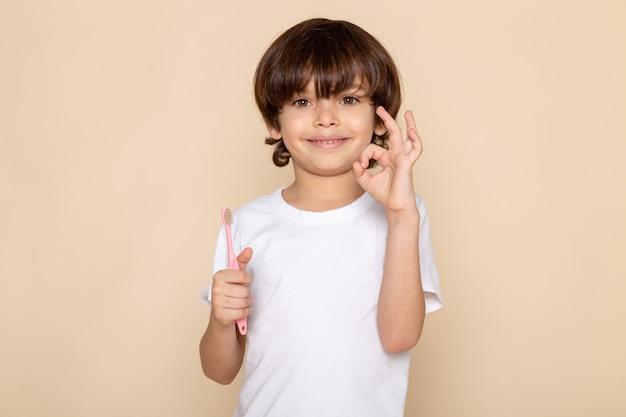 Vista frontal do retrato, sorrindo menino fofo adorável com escova de dentes na parede rosa