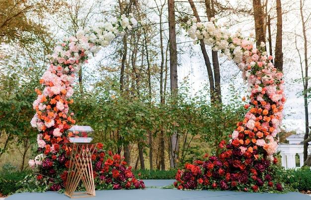 Vista frontal do rico arco decorado com adoráveis flores rosas frescas