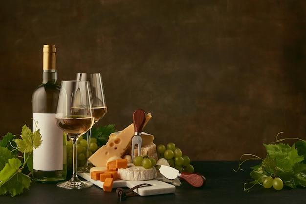 Vista frontal do saboroso prato de queijo com uvas e a garrafa de vinho, frutas e taças de vinho
