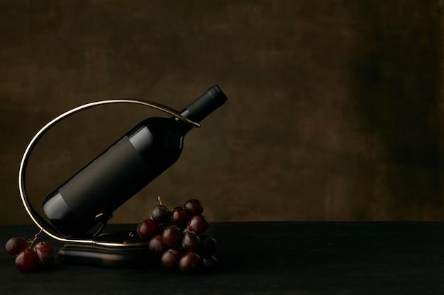 Vista frontal do saboroso prato de uvas com a garrafa de vinho no escuro