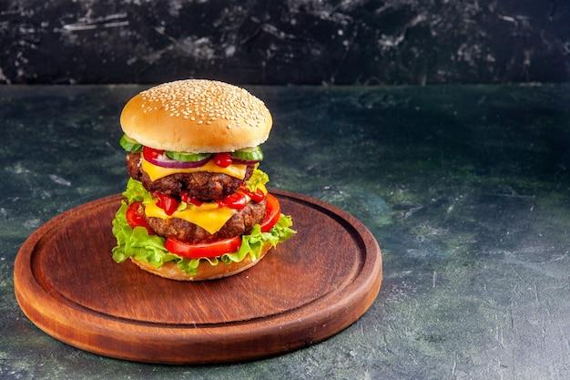Vista frontal do saboroso sanduíche em uma placa de madeira na superfície de cor escura