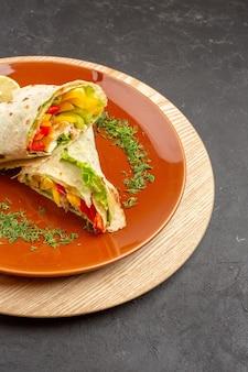 Vista frontal do sanduíche de carne deliciosa shaurma fatiado dentro de um prato marrom no espaço escuro