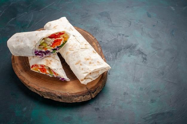 Vista frontal do sanduíche de carne, um sanduíche feito de carne grelhada no espeto com uma mesa azul escura