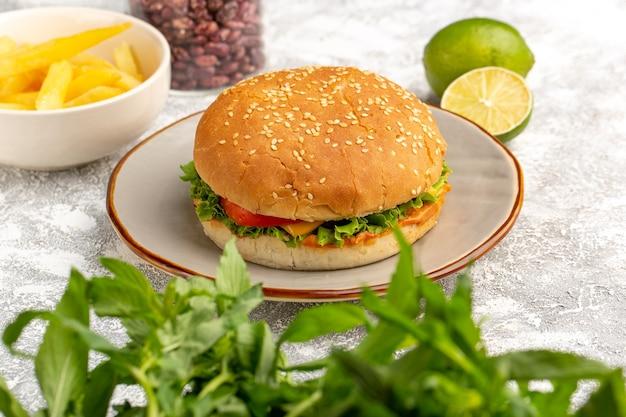 Vista frontal do sanduíche de frango com salada verde e vegetais dentro com batata frita e feijão com limão na mesa branca