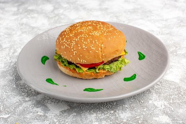 Vista frontal do sanduíche de frango com salada verde e vegetais dentro do prato na mesa de luz