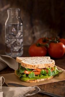 Vista frontal do sanduíche de torrada com verduras e tomates