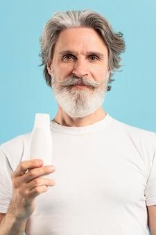 Vista frontal do sênior segurando hidratante