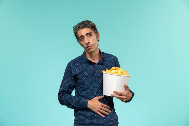Vista frontal do sexo masculino de meia-idade comendo cips na superfície azul