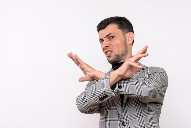 Vista frontal do sexo masculino jovem bonito de terno cruzando as mãos em pé sobre um fundo branco