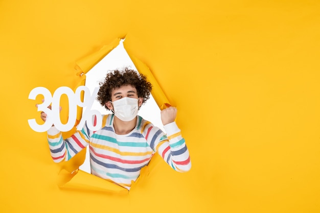 Vista frontal do sexo masculino jovem com máscara segurando nas cores amarelas, compras saúde covid foto pandêmica, venda de vírus