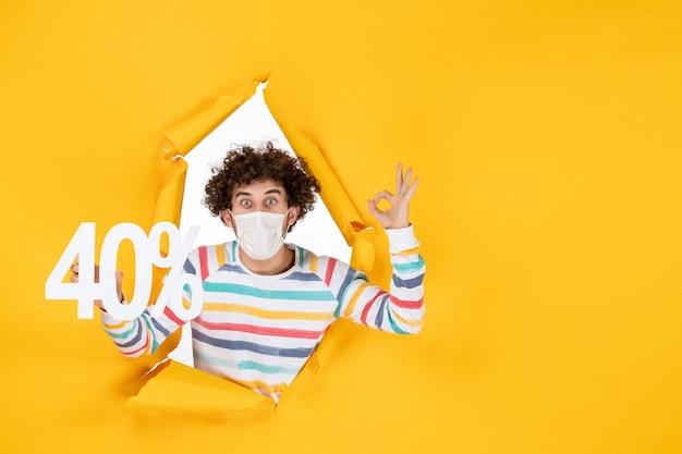 Vista frontal do sexo masculino jovem com máscara segurando uma escrita sobre cores pandêmicas de vírus amarelo.