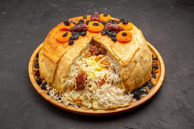 Vista frontal do shakh plov deliciosa refeição de arroz cozida dentro de massa redonda com passas no espaço cinza